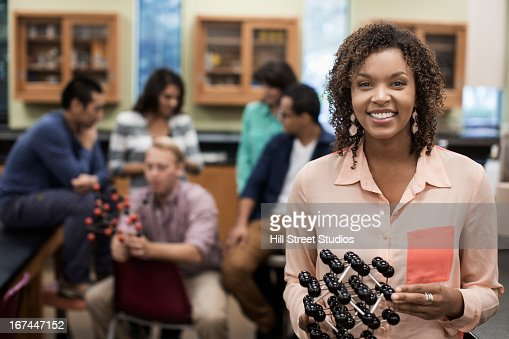 Mixed race student holding molecular model in lab classroom : Stock Photo