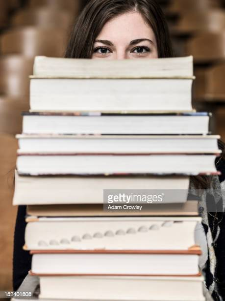 Mixed race student holding stack of books