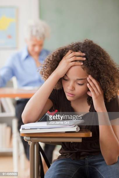 Mixed race student reviewing notes in classroom