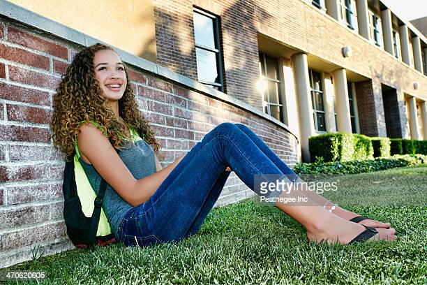 Mixed race student sitting on grass