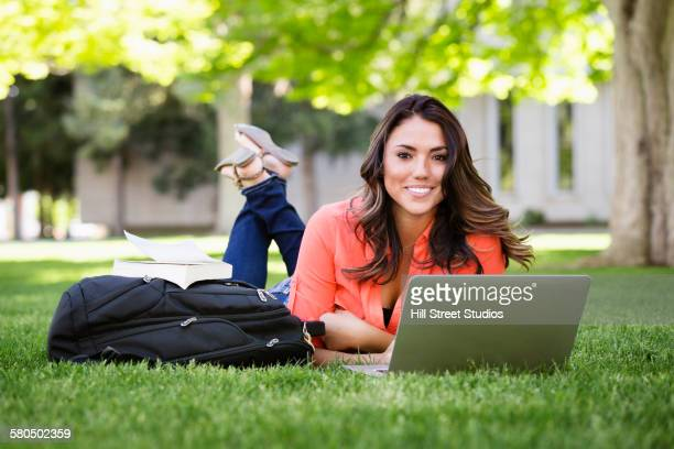 Mixed race student using laptop on college campus