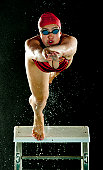 Mixed race swimmer diving off starting block