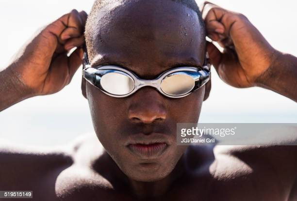 Mixed race swimmer putting on goggles