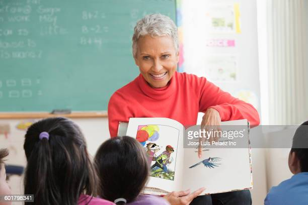 Mixed race teacher reading to class