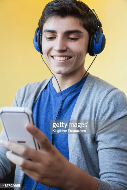 Mixed race teenage boy listening to headphones