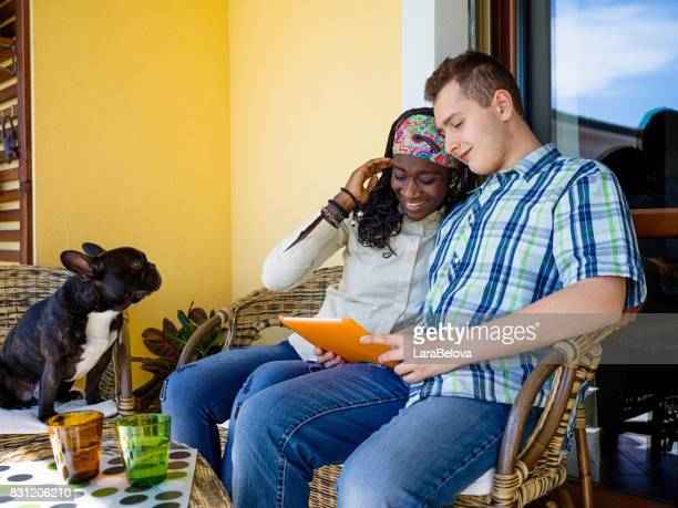 Mixed race teenage couple with touchpad on balcony