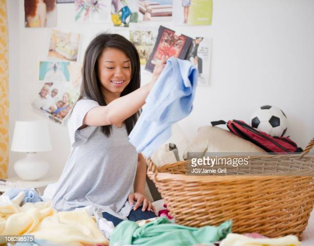 Mixed race teenage girl doing laundry on bed