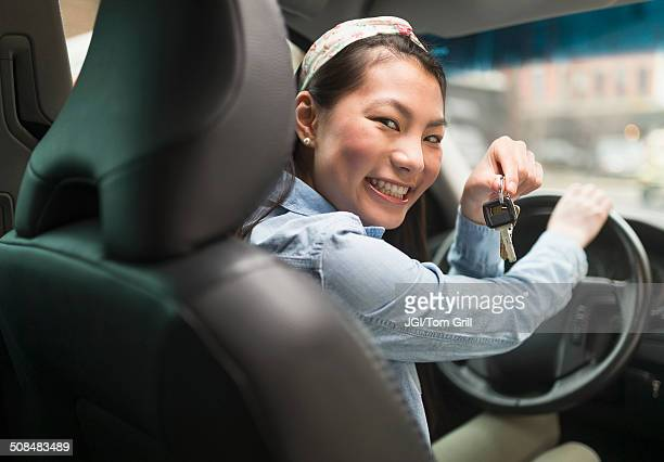 Mixed race teenage girl holding keys to car