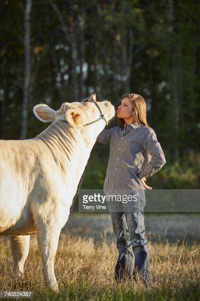 Mixed Race teenage girl kissing cow in field
