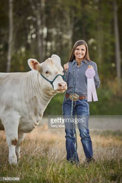 Mixed Race teenage girl posing with cow and award ribbon in field