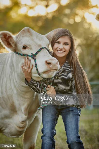 Mixed Race teenage girl posing with cow in field