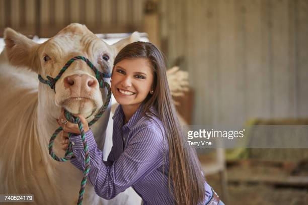 Mixed Race teenage girl posing with cow