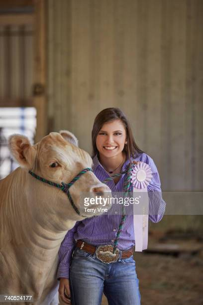Mixed Race teenage girl posing with cow showing award ribbon