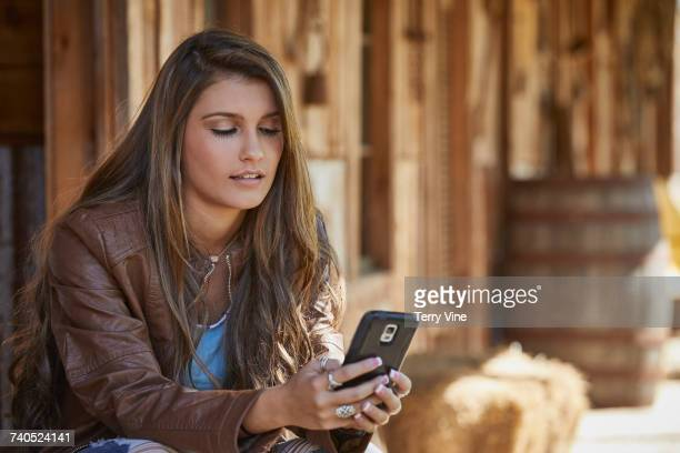 Mixed Race teenage girl texting on cell phone