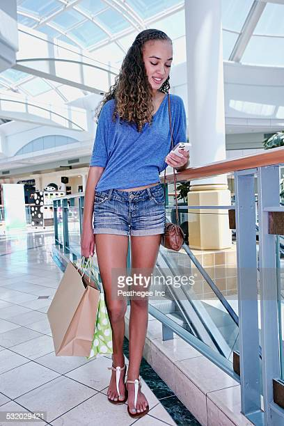 Mixed race teenage girl using cell phone and shopping at mall