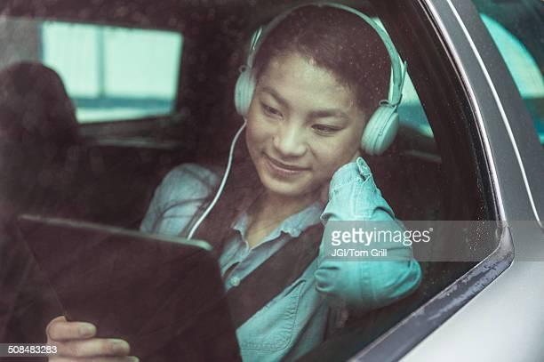 Mixed race teenage girl using digital tablet in backseat of car