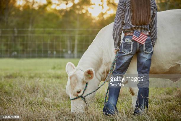 Mixed Race teenage girl with cow in field and American flag in pocket