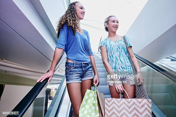 Mixed race teenage girls on escalator at shopping mall