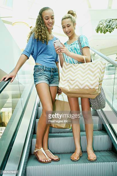 Mixed race teenage girls using cell phone on escalator at shopping mall