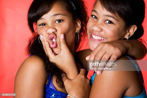Mixed race teenage twin girls making faces