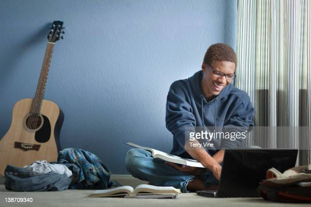 Mixed race teenager doing homework with laptop