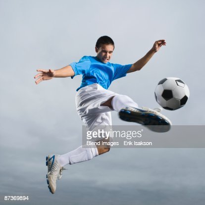 Mixed race teenager in mid-air kicking soccer ball