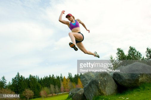 Mixed race teenager jumping from rock : Stock Photo