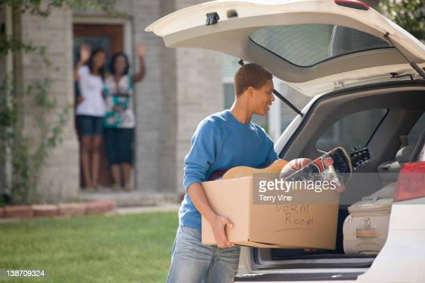 Mixed race teenager loading car for college
