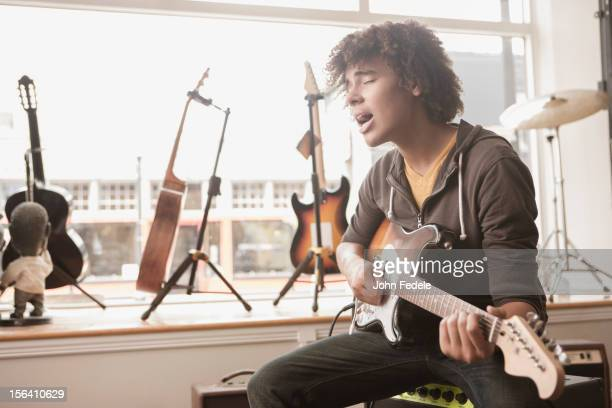 Mixed race teenager playing electric guitar and singing