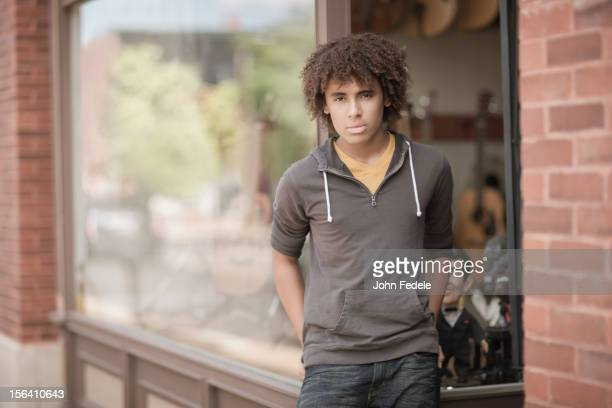 Mixed race teenager standing outside music store