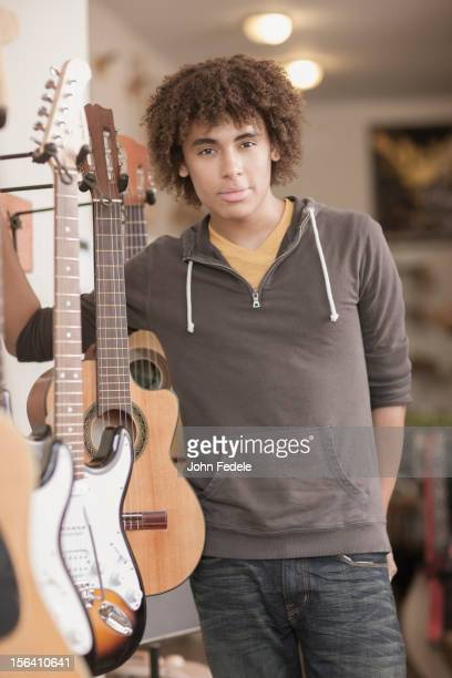 Mixed race teenager standing with guitars in music store