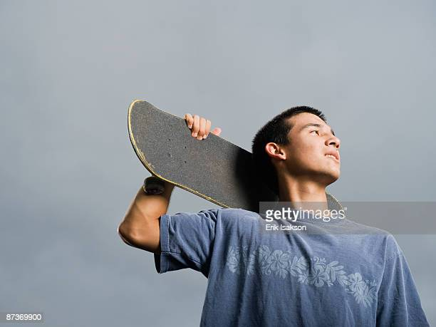 Mixed race teenager standing with skateboard