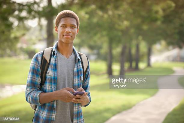 Mixed race teenager text messaging on cell phone