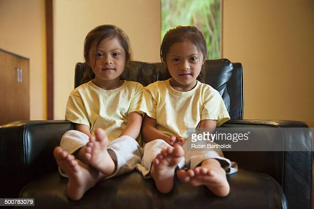 Mixed race twins with Down syndrome sitting in armchair