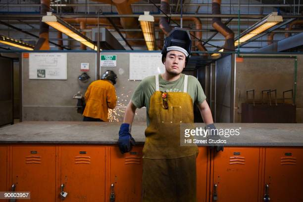 Mixed race welder leaning against lockers