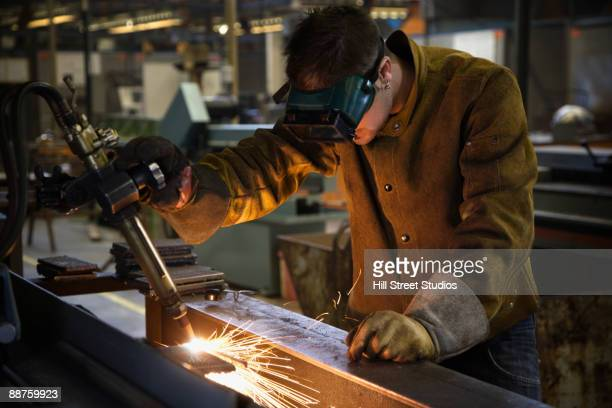 Mixed race welder working with torch