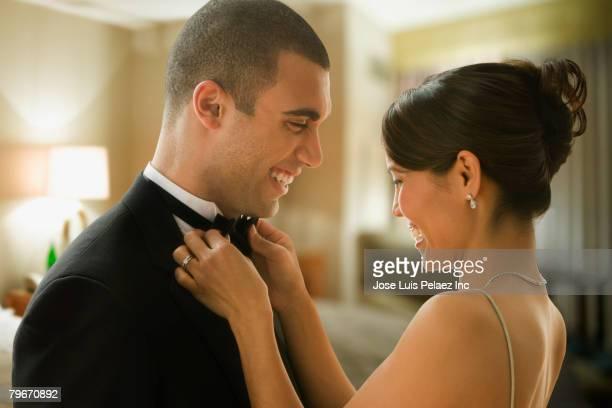 Mixed Race woman adjusting husband's bowtie