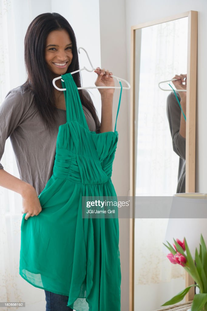 Mixed race woman admiring dress in mirror