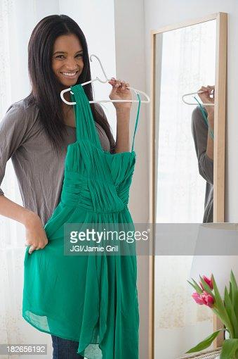 Mixed race woman admiring dress in mirror