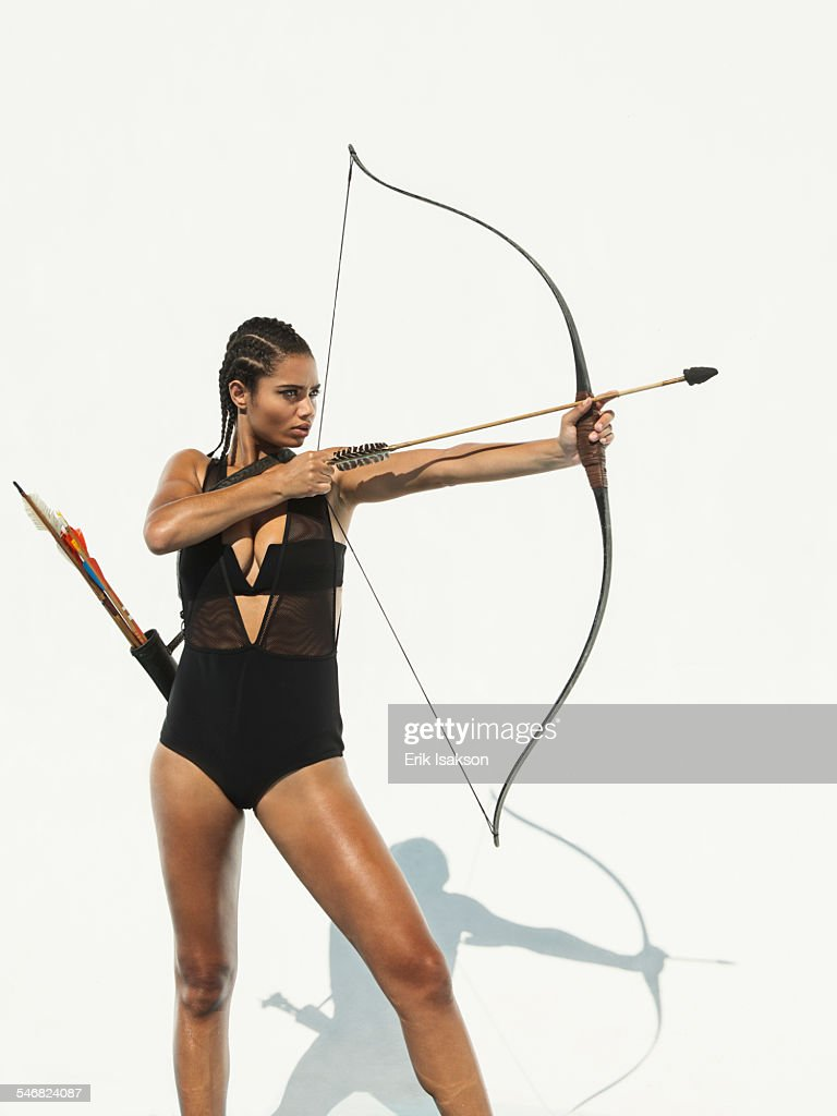 Mixed race woman aiming bow and arrow