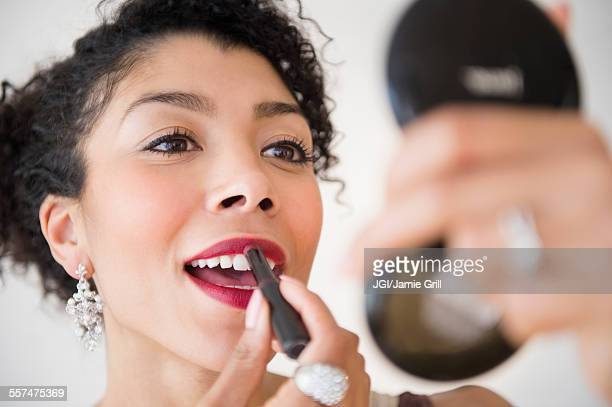 Mixed race woman applying lipstick in compact mirror