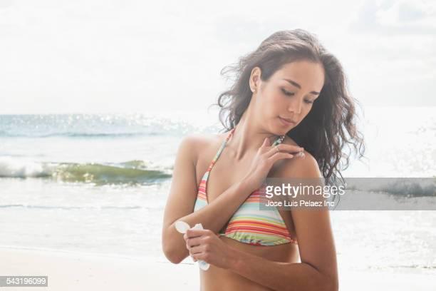 Mixed race woman applying sunscreen on beach