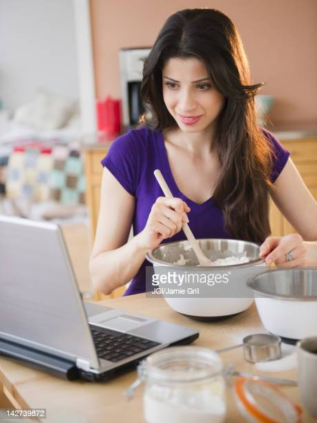 Mixed race woman baking and using laptop
