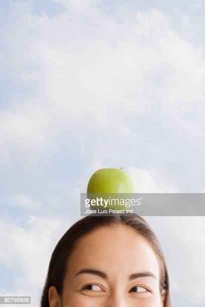 Mixed race woman balancing apple on head