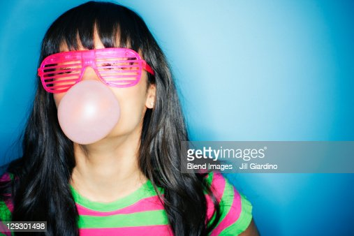 Mixed race woman blowing bubble with bubble gum : Foto de stock