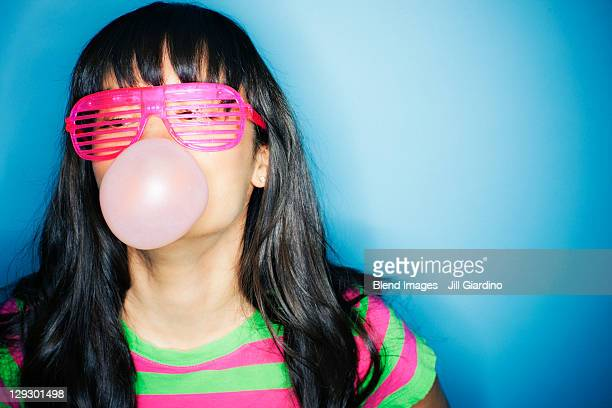 Mixed race woman blowing bubble with bubble gum