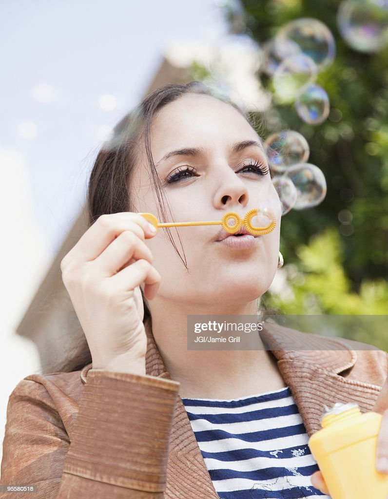 Mixed race woman blowing bubbles : Stock Photo