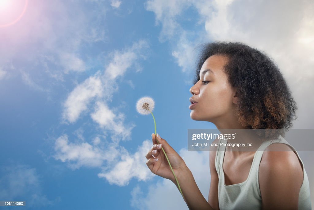 Mixed race woman blowing dandelion seeds : Stock Photo