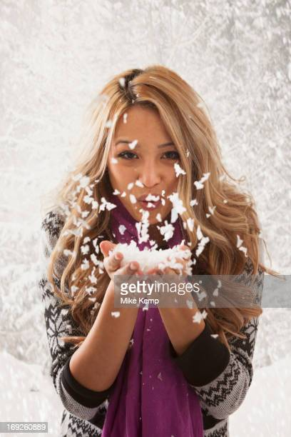 Mixed race woman blowing handful of snow