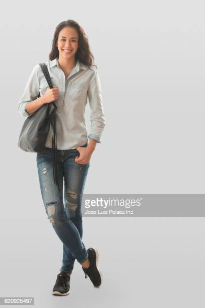 Mixed race woman carrying purse